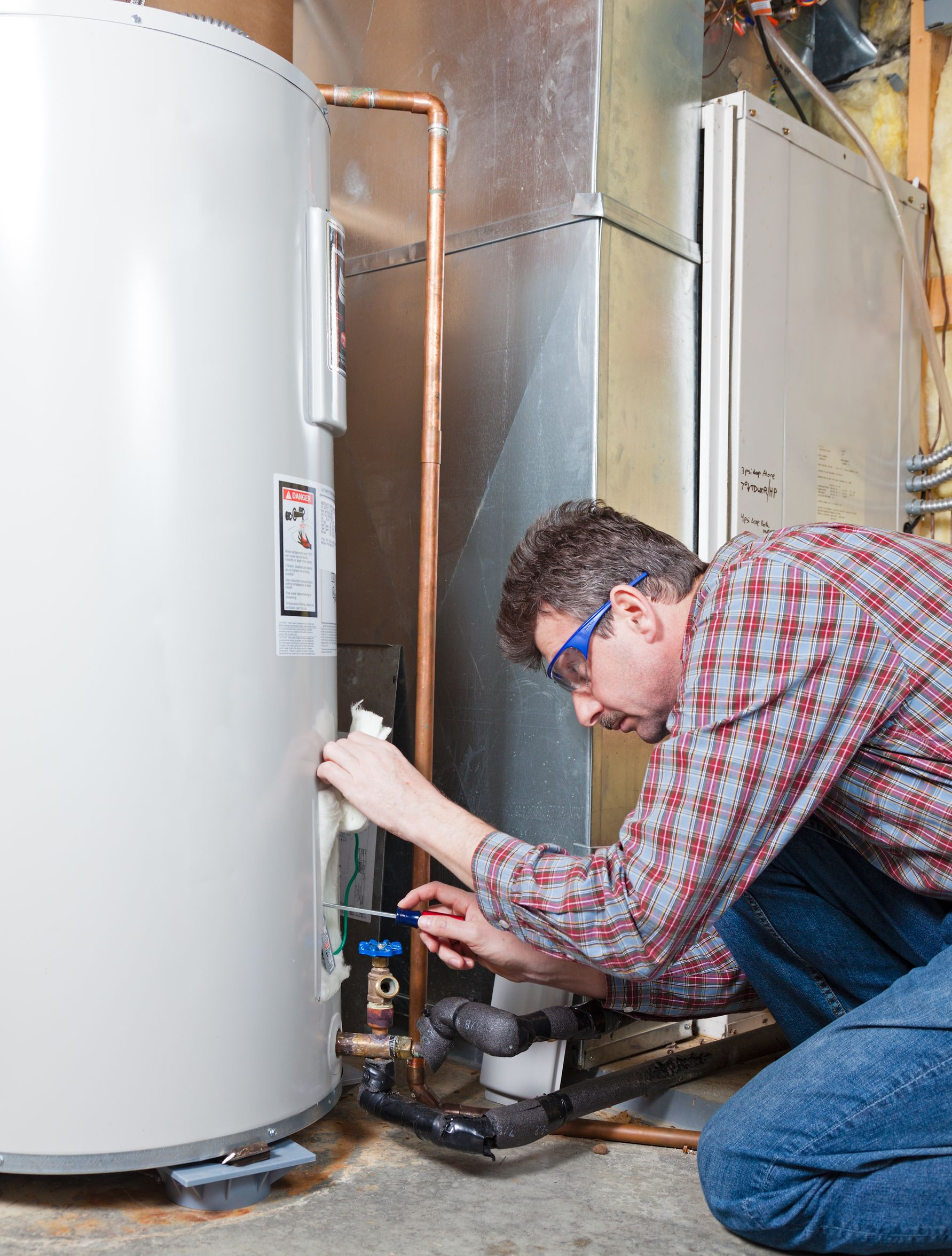 man repairing water heater